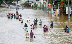 People walk through a flooded road after they moved out from their houses in Biyagama, Sri Lanka May 17, 2016. REUTERS/Dinuka Liyanawatte