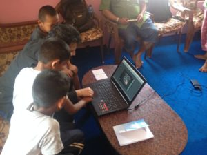 photograph of a young man and children crowded around a laptop computer