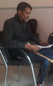 Rajan (name changed) reads a document while his make-shift bamboo walking stick rests on the chair he is seated on